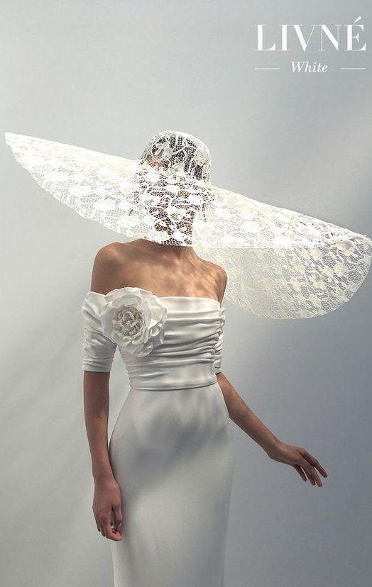 Свадебное платье цвета слоновой кости без рукавов, декольте с открытыми плечами, складчатые детали, крупный цветок из крепа. Шляпка невесты - оригинальное завершение образа. Livné White. Коллекция 2020