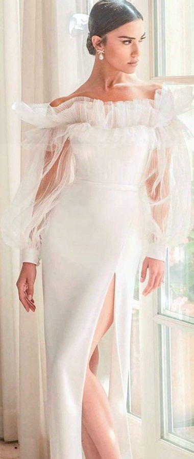 Свадебное платье приталенного силуэта с рюшами на декольте и длинными воздушными рукавами с манжетами на пуговицах. Юбка дополнена асимметричным разрезом, открывающим ногу выше колена. Дизайнер Alon Livné. Коллекция свадебных платьев 2020