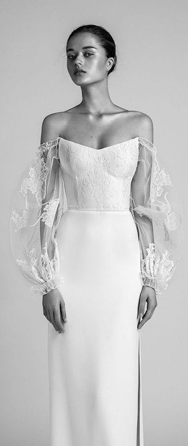 Свадебное приталенное платье с прямой юбкой и длинными рукавами. Лиф, открывающий плечи вырезом «лодочка», декорирован кружевом. Такие же узоры покрывают прозрачные пышные рукава до запястий. Wedding Dress Trends With Livné White 2020