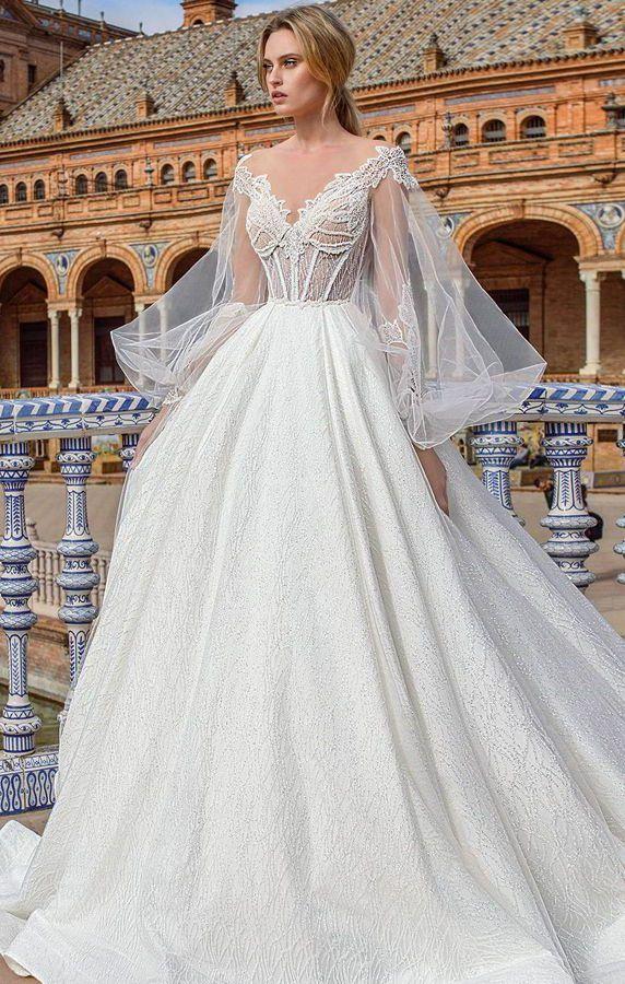 Женственное свадебное платье с приталенным силуэтом и расклешенной пышной юбкой. Лиф с v-образным декольте и длинные, пышные, прозрачные рукава. Ricca Sposa 2020 Wedding Dresses