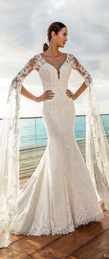 Длинное свадебное платье с кружевные рукавами три четверти, от которых спускаются книзу длинные прозрачные кейпы с вышивкой из фатина. Cosmobella Collection 2020