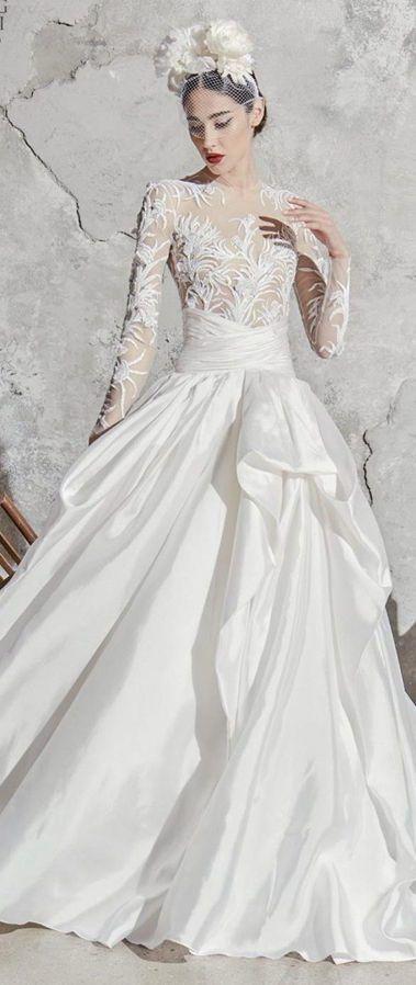Пышное, кружевное, свадебное платье с длинными рукавами вместе с украшением на голову с крупными цветами. Свадебная коллекция Zuhair Murad весна 2020