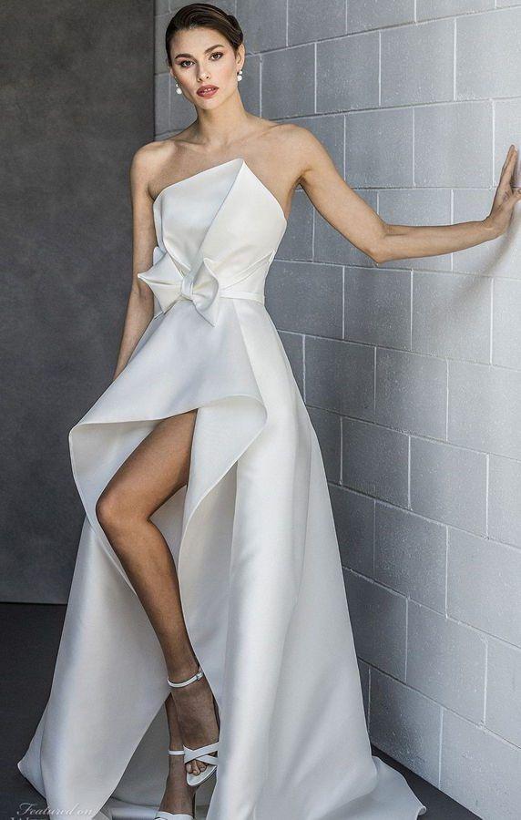 Элегантное, открытое, свадебное платье с укороченной спереди асимметричной юбкой и красивым бантом на талии от Valentini Spose. Spring 2020 Bridal Collection