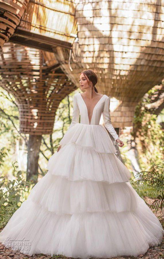Пышное свадебное платье с длинными рукавами, глубоким вырезом декольте и многоярусной юбкой, выполненной из плиссированных оборок, начинающихся от талии и спускающихся книзу. Milla by Lorenzo Rossi 2020 Wedding Dresses