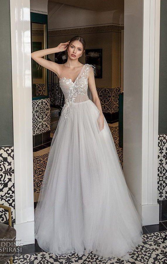 Свадебное платье цвета айвори с бретелью на одно плечо сочетает в себе все необходимые черты безупречного наряда – элегантность, романтику, торжественность. Пышная юбка с легкими вертикальными волнами и облегающий асимметричный верх акцентирует фигуру, очерчивая область декольте фигурным V-образным вырезом. Romanzo by Julie Vino The Royal Bridal Spring 2020