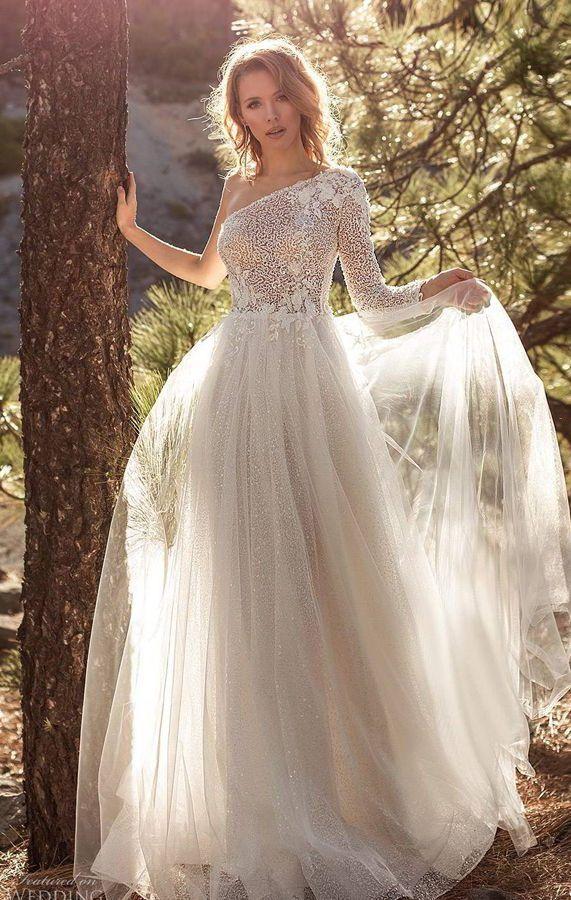 Красивое свадебное платье с воздушной трапециевидной юбкой и асимметричным верхом. Полупрозрачный лиф с узорами скроен на одно плечо и переходит в длинный прямой рукав. Новая коллекция 2020