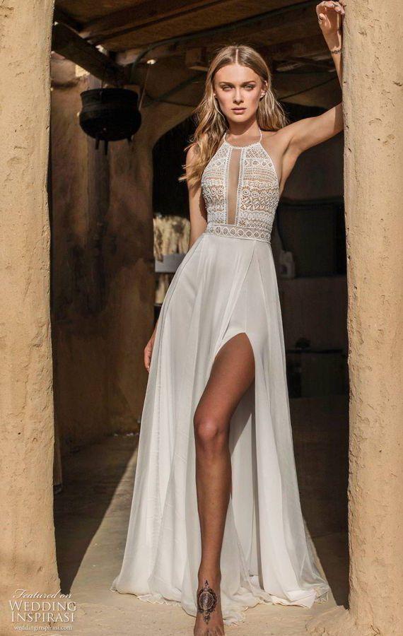 Свадебное платье в греческом стиле с вырезом халтер и прямоугольным выреза в области декольте украшены по краю каймой из мерцающего бисера. Легкая расклешенная юбка с асимметричным разрезом переходит в шлейф. Asaf Dadush 2020 Wedding Dresses
