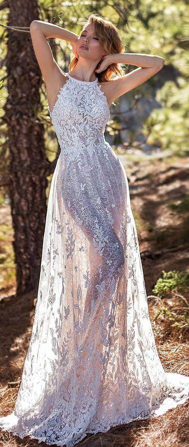 Утонченный силуэт невесты мягко подчеркивает прилегающее свадебное платье из тонкой прозрачной ткани с вырезом халтер. Платье щедро украшено роскошной аппликацией из фактурного кружева.