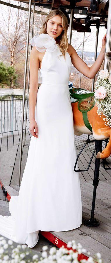 Элегантное свадебное платье с горловиной «халтер», украшенное крупным цветком. Прямая атласная юбка без декора оканчивается шлейфом. Свадебная коллекция Lela Rose весна-лето 2020