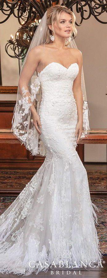 Изысканное свадебное платье-бюстье со шлейфом, украшенным перьями.