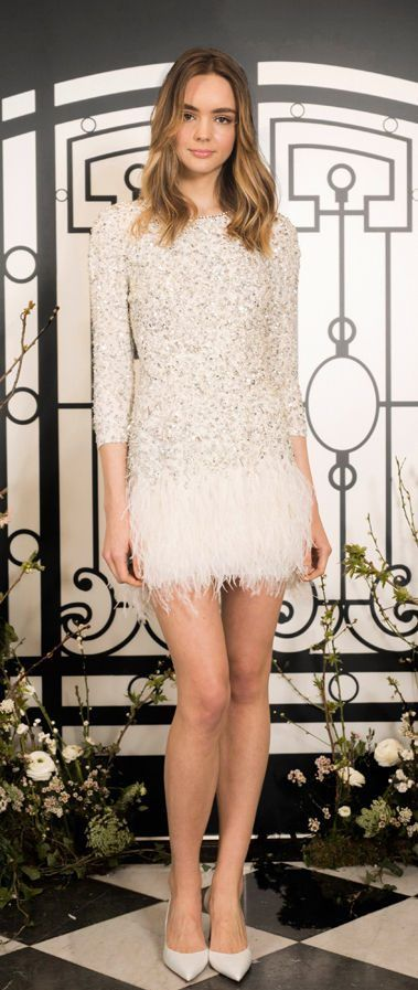 Короткое, облегающее свадебное платье-футляр из плотной белой ткани декорировано серебристыми элементами. Низ украшен широкой тесьмой из перьев. Рукав – ниже локтя. Новая коллекция от Jenny Packham 2020.
