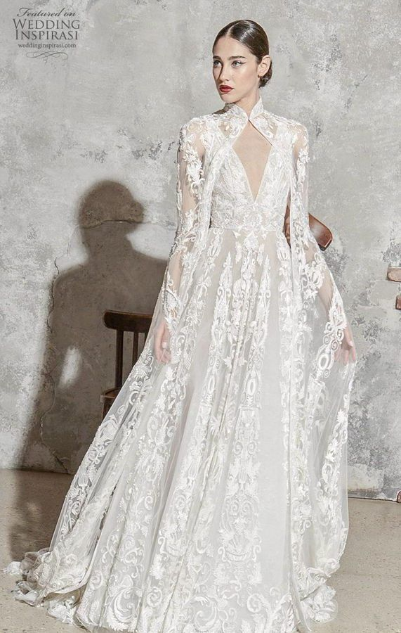 Длинное свадебное, белое, гипюровое платье А-силуэта, с глубоким V-образным вырезом от Zuhair Murad. Накидка придает образу легкой консервативности. Коллекция 2020.